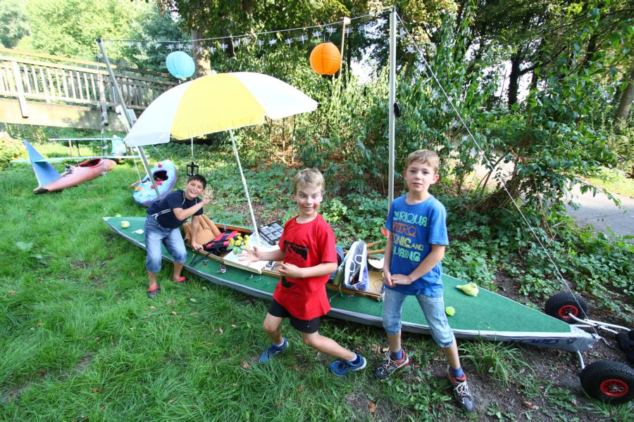 Gjemal, Mads und Jannes legen den Rollrasen auf's Faltboot und stellen den Sonnenschirm auf.