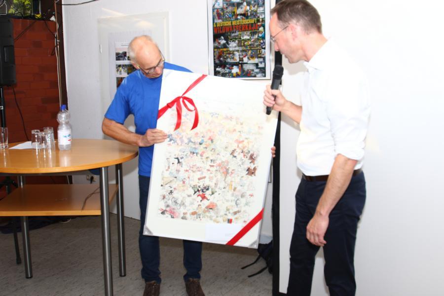 """Aber auch ein richtiges Geschenk überreichte Herr Mettenborg: Ein Poster mit den gezeichneten """"Highlights der Stadt Rheda-Wiedenbrück"""". Natürlich fehlen auch die Kanuten auf dieser Zeichnung nicht."""